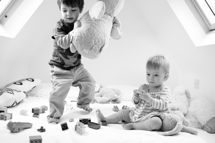 Brother and sister playing during a family photo session in London