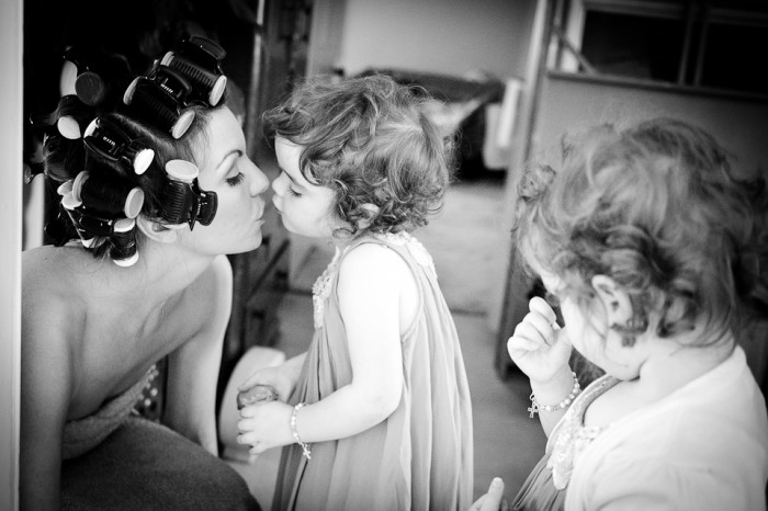 Documentary-style, black and white image of bride kissing her twin daughters during bridal preparations.