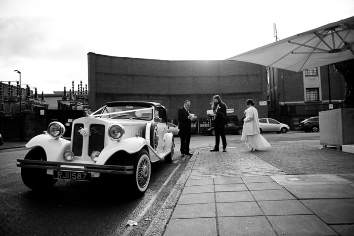 Black and white photograph of wedding couple getting into vintage car