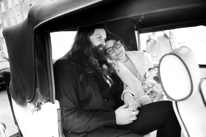 Bride and groom in vintage car at London wedding
