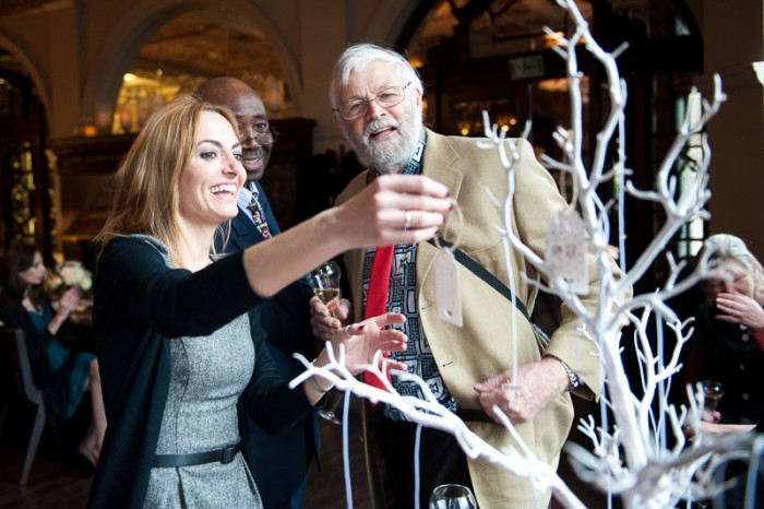 Guests hanging wishes on wishing tree at London wedding