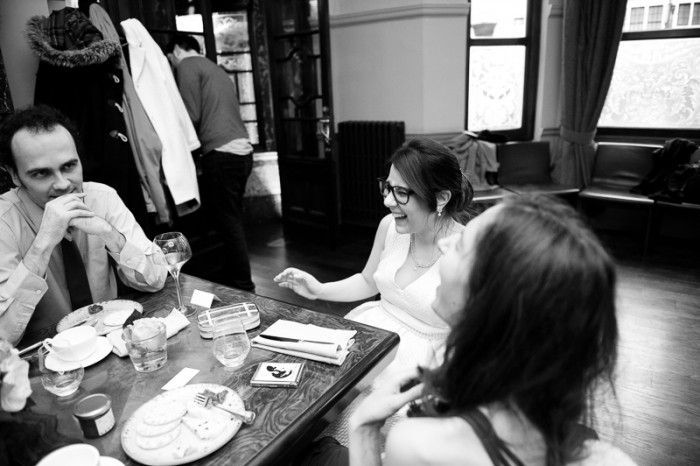 Candid photograph of bride laughing with friends at London pub wedding