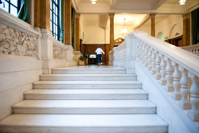 Little boy running on marble staircase at Camden Town Hall