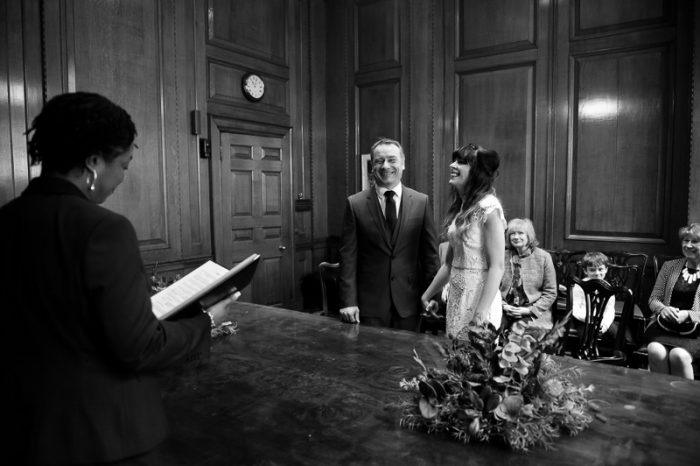 Informal black and white photograph of bride and groom laughing during wedding ceremony at Camden Hall
