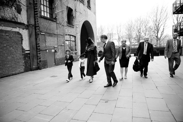 Relaxed photograph of family walking to the Oxo Tower to celebrate a winter wedding
