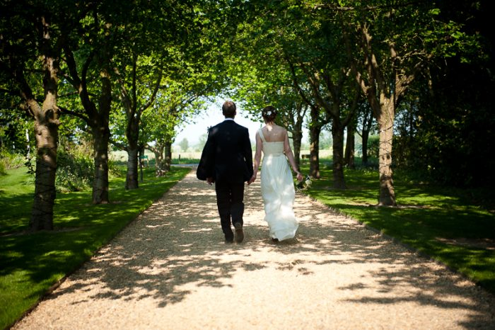 Bride and groom walking hand in hand at South Farm