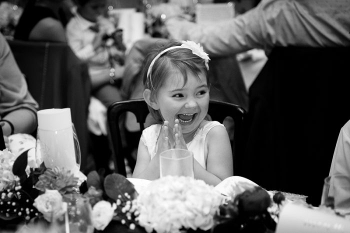 Candid wedding photo of little girl laughing during the speeches