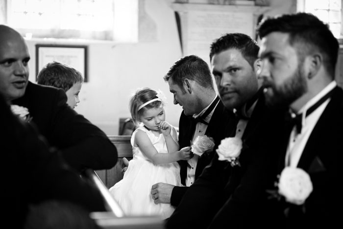 Black and white photo of little girl at church wedding sitting with ushers and best men