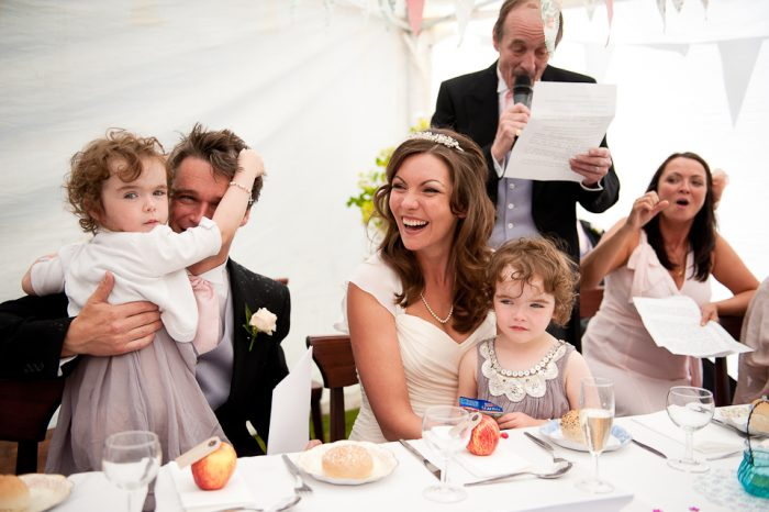 Reportage wedding photograph of bride and groom during the speeches at a marquee wedding