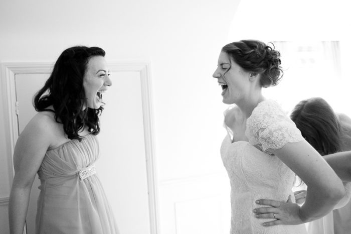Bride and best friend laughing during bridal preparations