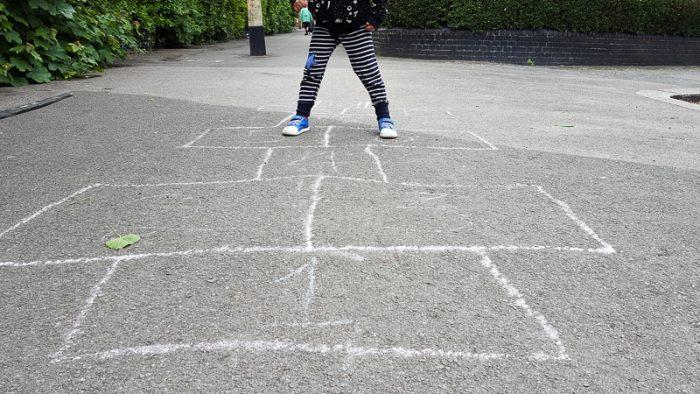 Boy playing hopsotch