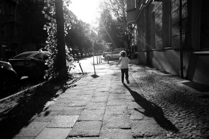 Little boy running through the streets of Berlin