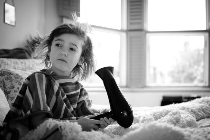 Child blowdrying hair