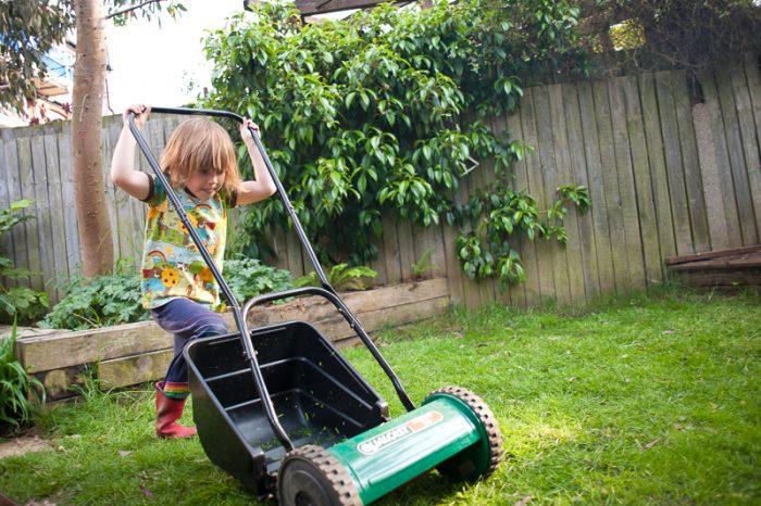 Boy mowing grass