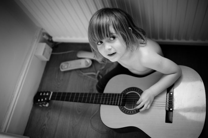 Black and white photo of boy with guitar