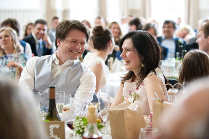 Natural photograph of couple enjoying the speeches at a wedding at Lyne Village Hall