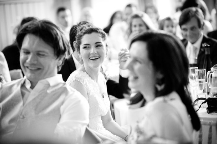 Bride smiling during the speeches at Lyne Village Hall wedding