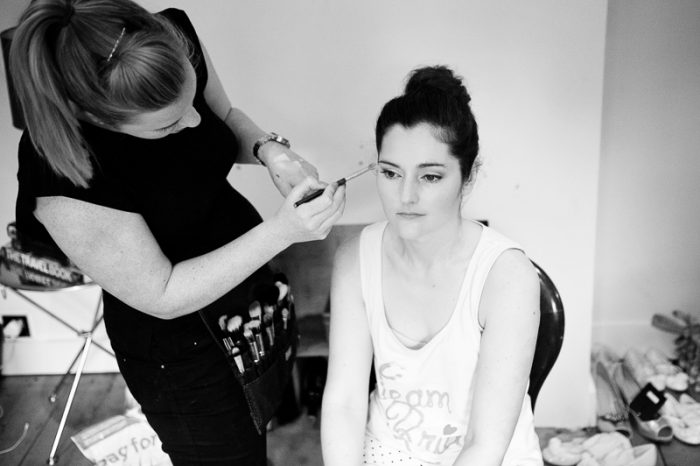 Documentary-style photograph of bride putting on make-up