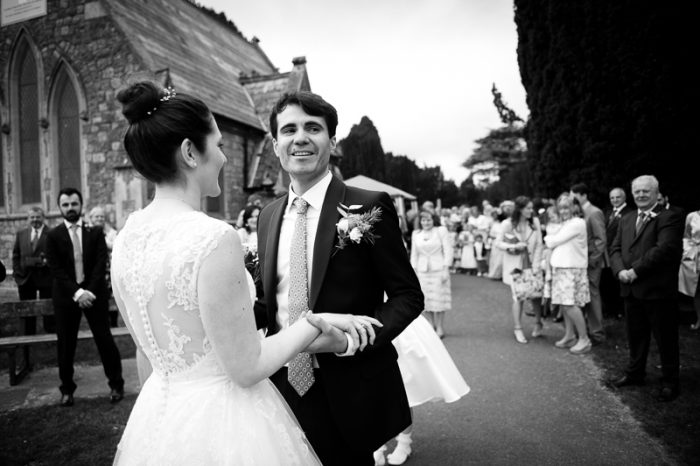 Bride greets groom outside the Greek Orthodox church in Englefield