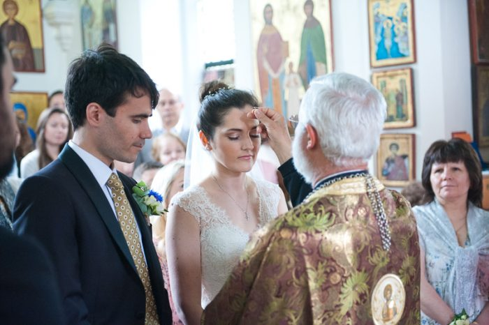 Bride and groom during Greek Orthodox wedding ceremony in Surrey