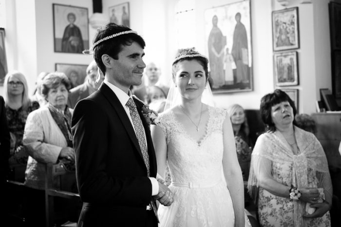 Black and white photograph of bride and groom during Greek Orthodox wedding ceremony