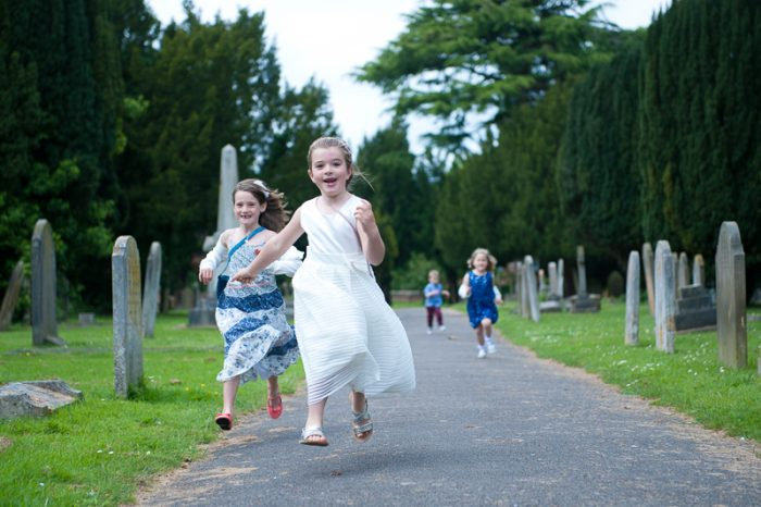 Group of children running at church wedding in Surrey