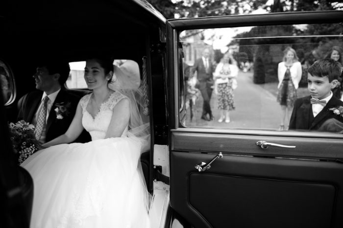 Bride and Groom in car with ringbearer looking on