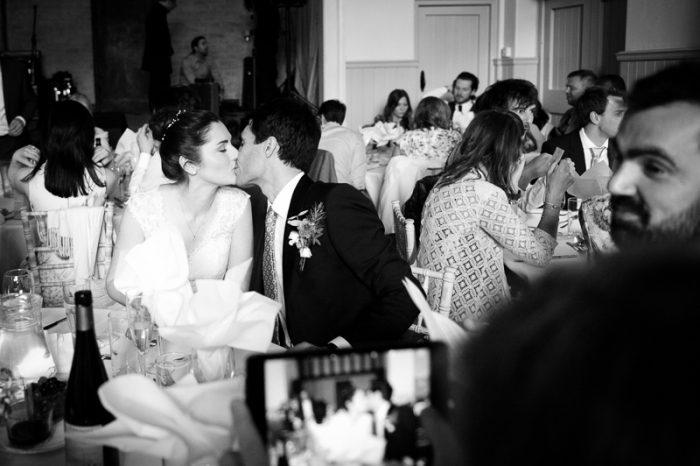 Bride and groom kissing at village hall wedding