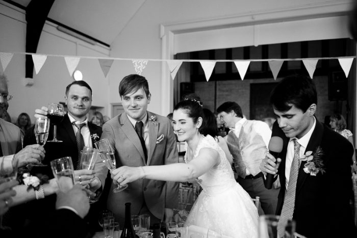 Bride raises a glass at Lyne Village Hall wedding