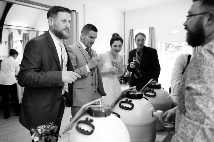 Bride and guests enjoying homebrewed beer at Village Hall wedding