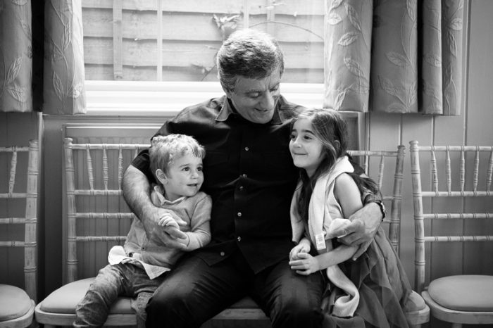 Reportage photo of grandpa hugging grandkids at village hall wedding