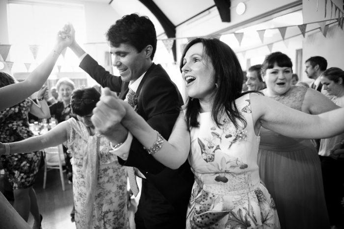 Greek dancing at village hall wedding