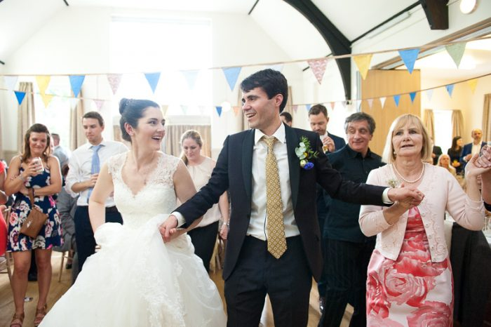 Bride and groom joining in the Greek dancing