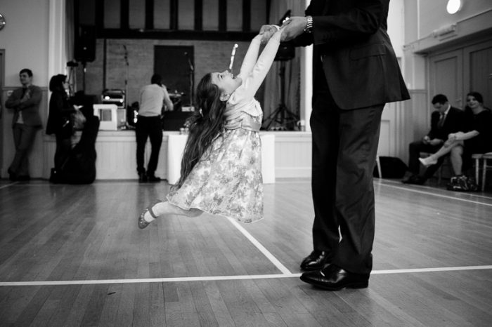 Little girl on dancefloor at village hall wedding in Surrey