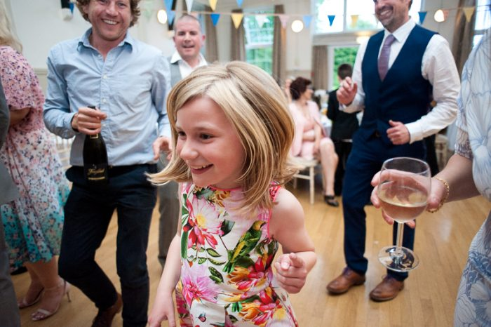 Little girl dancing at village hall wedding