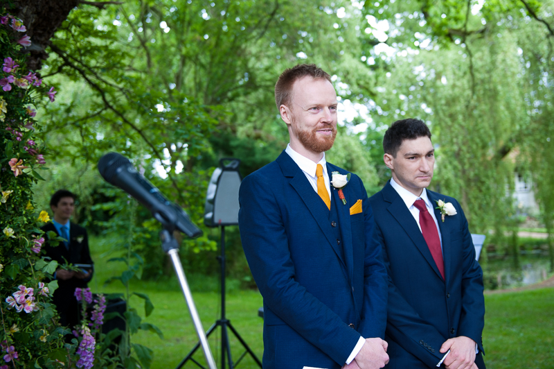 Groom seeing bride for the first time at outdoor wedding ceremony