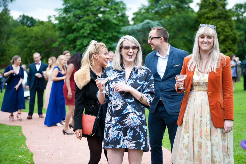 Documentary-style wedding photo of guests laughing