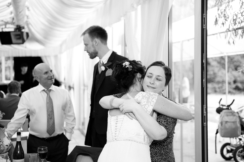 Candid photo of bride hugging guest