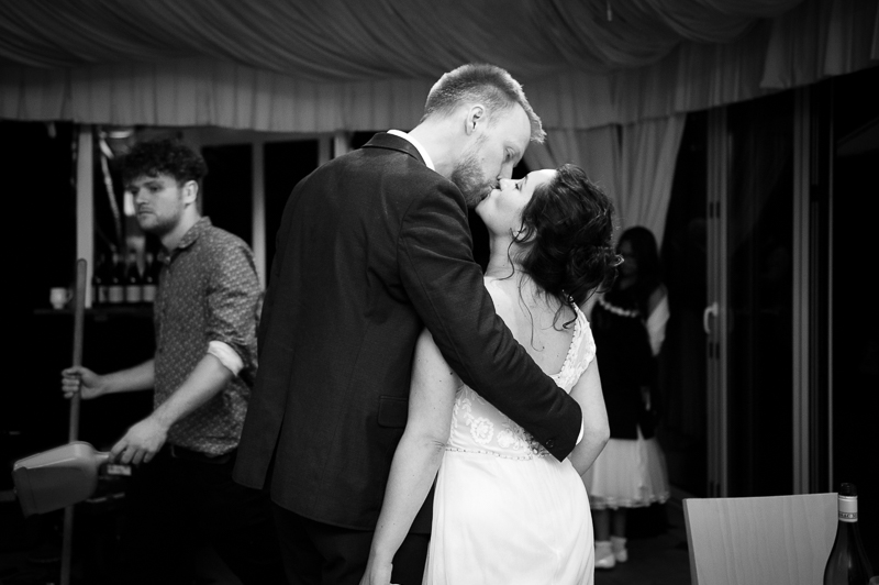 Candid shot of bride and groom kissing