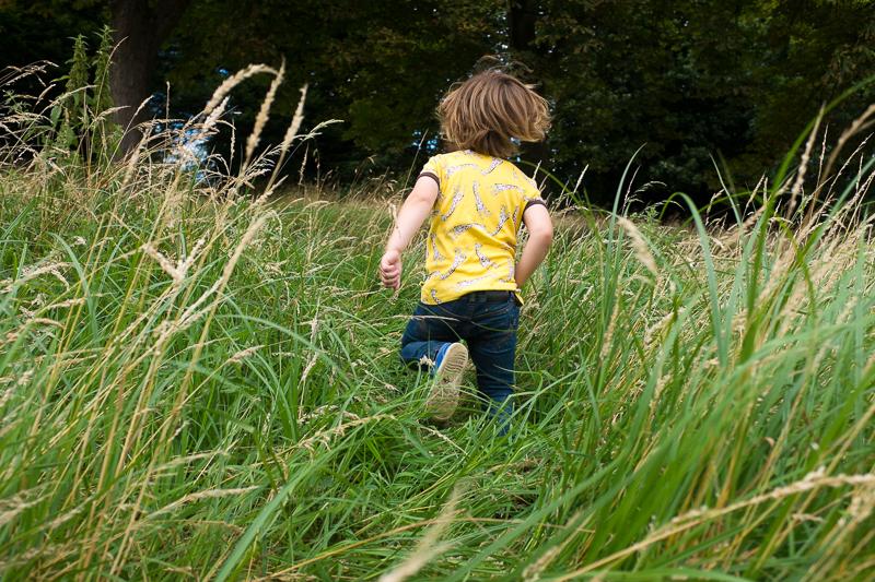 Child running through long grass in Alexandra Park