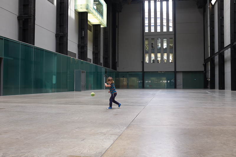 Child playing ball in the turbine hall