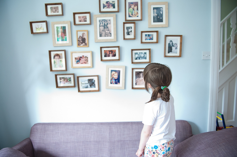 Girl in living room looking at family photographs