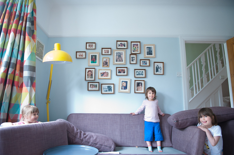 Little girl standing on couch during family photo session in Palmers Green