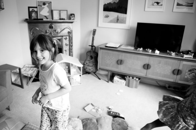 Little girl running around in the lounge during natural family portrait in Palmers Green