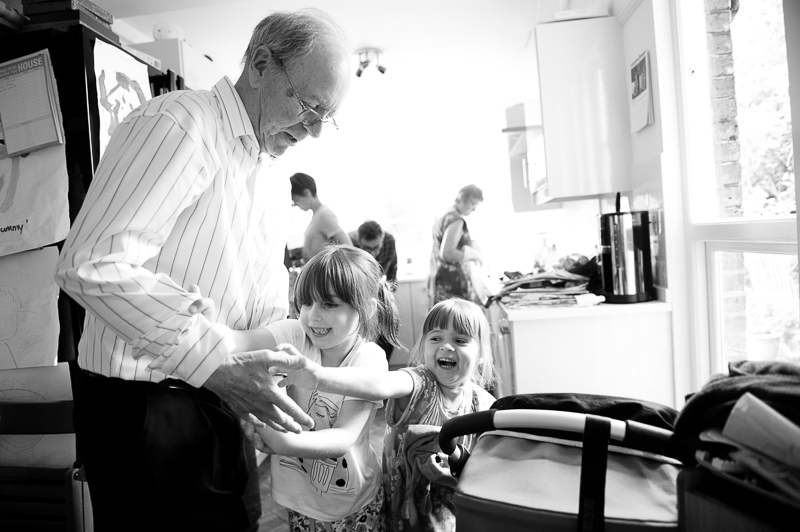 Granddaughters playing with grandpa during family photo shoot