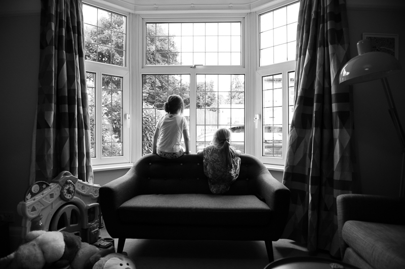 Cousins looking out of the window during family portrait in Palmers Green