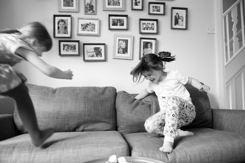 Cousins jumping on the sofa during documentary family portrait session in North London