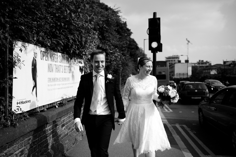 Bride and groom walking along the streets of Stoke Newington