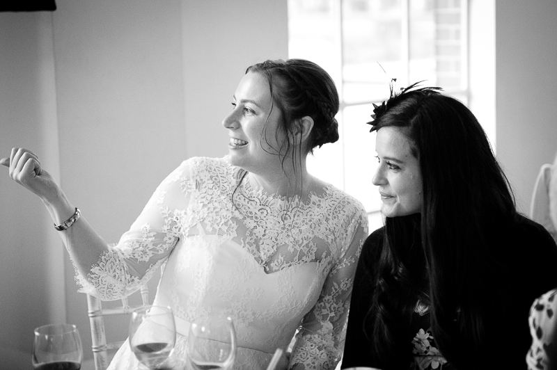 Reportage photograph of bride talking to friend at wedding reception