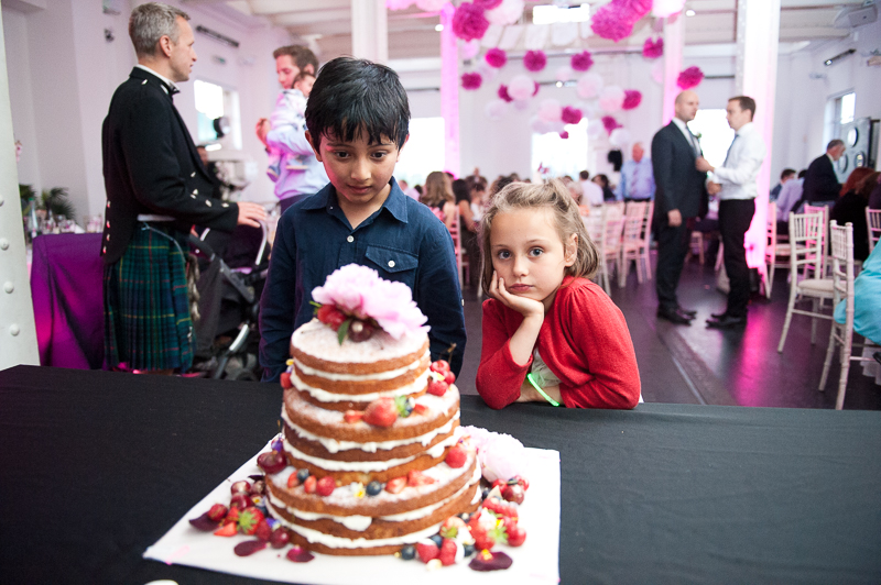 Kids eyeing up a wedding cake with summer fruit